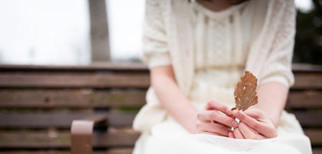 枯れ葉を持って座っている女性